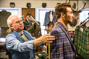 Image of a man being fitted for a tartan suit by a tailor